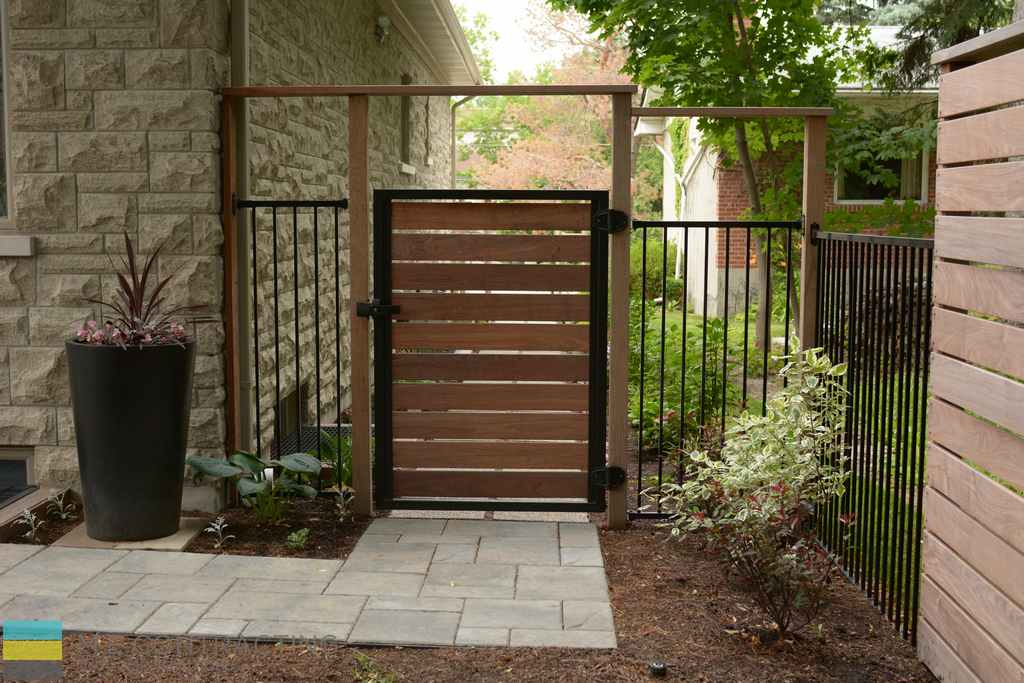 Interlocking walkway, cedar fence and gate with aluminum fence, landscaping