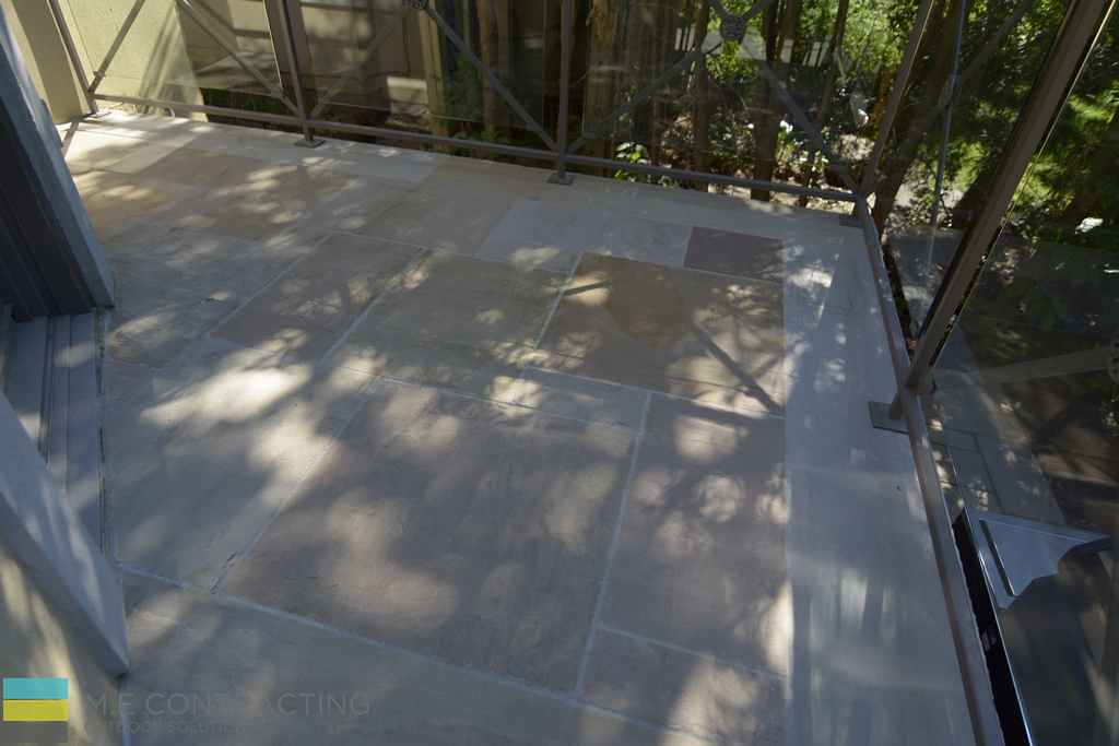 Interlocking stone deck, tempered glass railings, wrought iron frames