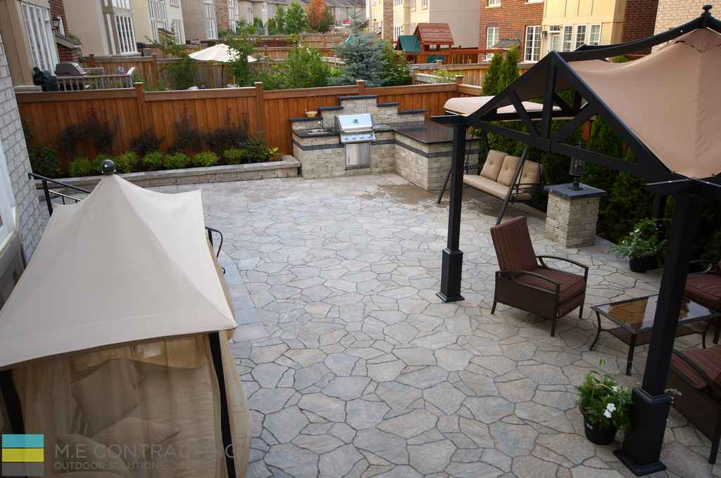 Landscaping, coping flagstone, retaining wall, interlocking patio, stainless steel outdoor kitchen, aluminum pergola, IPE fence