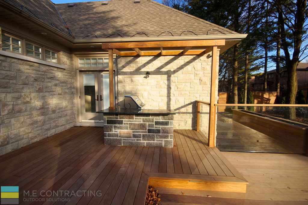 Stone veneer, interlocking, landscaping, outdoor kitchen, cedar deck, tempered glass railings with cedar posts, pergola, coping flagstone counter top
