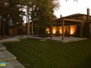Landscaping, cedar fence, lighting, pergola, stone patio, fiberglass pool