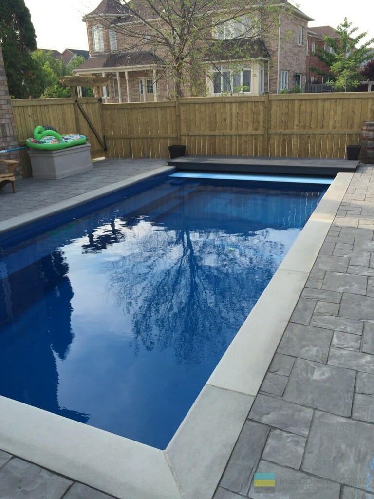 Fiberglass pool, interlocking stone and cedar fence.