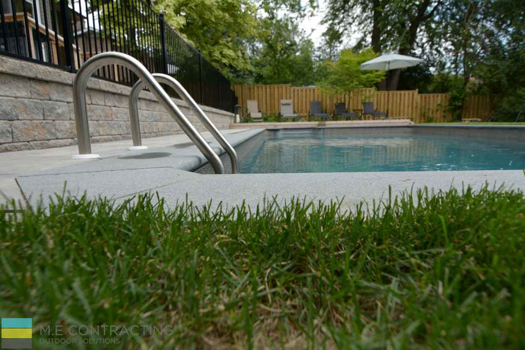 Fiberglass pool, coping stone, landscaping, interlocking retaining wall, stone walkway, cedar deck with aluminum railings.